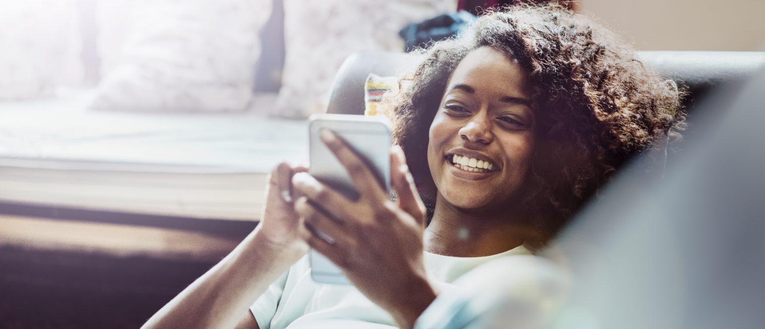 Happy woman using mobile phone on sofa